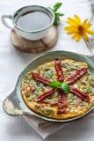 Traditionell fritatta med torra tomater i en gjutjärnpanna Vit bakgrund, kopieringsutrymme fotografering för bildbyråer