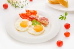 Traditionell frukost med bacon, stekte ägg och bröd Arkivbilder