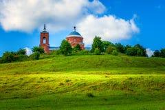 Traditionell gammal rysskyrka - sommarlandskap med blå himmel, gröna kullar med gräs arkivbilder