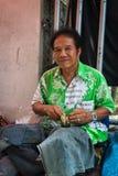 Traditionell gataskomakare som ler sammanträde Royaltyfria Foton