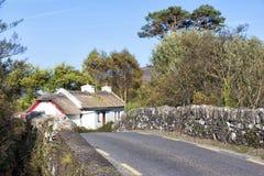 Traditionell halmtäckt stuga vid bron i Irland Arkivbild