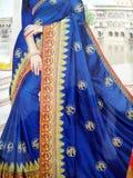 Traditionell handgjord vit, r?d/rosa bl? indisk siden- sari /saree med guld- detaljer, kvinnabruk att b?ra p? den Onam festivalen arkivbilder