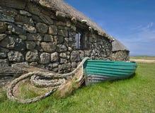 Traditionell Hebridean blackhouse med det halmtäckte taket, träfiskebåten och det rullade ihop repet Royaltyfria Foton
