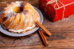 Traditionell hemlagad kaka som dekoreras med kanelbruna pinnar Röd gåvaask Arkivbilder