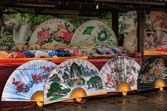 Traditionell hemslöjdkines fläktar imajing för withs av landskapet och blommar på marknaden i Yangshuo, Kina arkivfoto