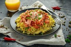 Traditionell Indier-engelsk kedgereefrukost: basmati ris med ägget benedict och den varma rökte söta chililaxen fotografering för bildbyråer