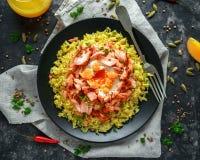 Traditionell Indier-engelsk kedgereefrukost: basmati ris med ägget benedict och den varma rökte söta chililaxen arkivbilder