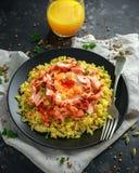Traditionell Indier-engelsk kedgereefrukost: basmati ris med ägget benedict och den varma rökte söta chililaxen royaltyfri fotografi