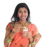 Traditionell indisk kvinna som äter yoghurt Fotografering för Bildbyråer