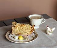 Traditionell inställning för påskfrukosttabell med den easter kakan, en kopp kaffe arkivbild