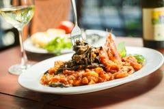 Traditionell italiensk maträtt - svart tagliatelle med skaldjur royaltyfri bild