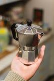 Traditionell italiensk mokakrukakaffebryggare på handen i köket Arkivbild