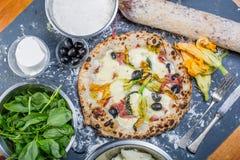Traditionell italiensk pizza med mozzarellaen, salami, ricotta och pumpa blommar Royaltyfri Fotografi