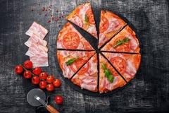 Traditionell italiensk pizza med mozzarellaost, skinka, tomater royaltyfria bilder