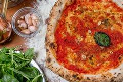 Traditionell italiensk pizza med tomatsås, vitlök och basilika, nolla Arkivfoto
