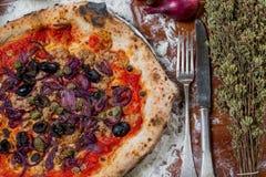 Traditionell italiensk pizza med tonfisk, lökar, hoppar omkring och oliv, nolla Royaltyfri Bild