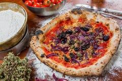 Traditionell italiensk pizza med tonfisk, lökar, hoppar omkring och oliv, nolla Arkivbild