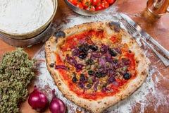 Traditionell italiensk pizza med tonfisk, lökar, hoppar omkring och oliv, nolla Arkivfoto
