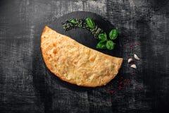 Traditionell italiensk pizzacalzone med ingredienser på en sten och en mörk träskrapad bakgrund arkivbild