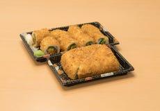 Traditionell japansk mat - del av flera sorter av sushi, med sushirostat bröd, snittet in i fyra stycken på magasin med wasabi oc Fotografering för Bildbyråer