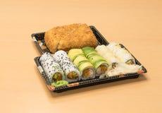 Traditionell japansk mat - del av flera sorter av sushi, med sushirostat bröd, snittet in i fyra stycken på magasin med wasabi oc Arkivbilder