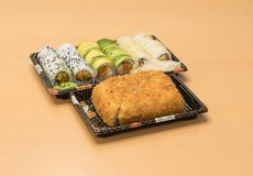 Traditionell japansk mat - del av flera sorter av sushi, med sushirostat bröd, snittet in i fyra stycken på magasin med wasabi oc Royaltyfri Bild