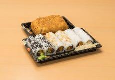 Traditionell japansk mat - del av flera sorter av sushi, med sushirostat bröd, snittet in i fyra stycken på magasin med wasabi oc Royaltyfri Foto