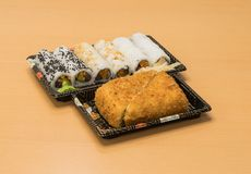 Traditionell japansk mat - del av flera sorter av sushi, med sushirostat bröd, snittet in i fyra stycken på magasin med wasabi oc Arkivbild