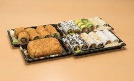 Traditionell japansk mat - del av flera sorter av sushi, med sushirostat bröd, snittet in i fyra stycken på magasin med wasabi oc Royaltyfria Bilder