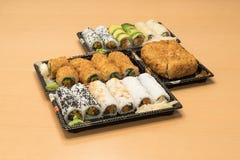 Traditionell japansk mat - del av flera sorter av sushi, med sushirostat bröd, snittet in i fyra stycken på magasin med wasabi oc Arkivfoton