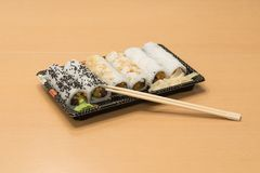 Traditionell japansk mat - del av flera sorter av sushi med wasabi och den inlagda ingefäran på ett magasin och med träpinnar Arkivfoton