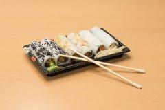 Traditionell japansk mat - del av flera sorter av sushi med wasabi och den inlagda ingefäran på ett magasin och med träpinnar Arkivbilder