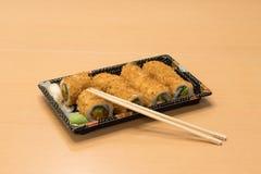 Traditionell japansk mat - del av flera sorter av sushi med wasabi och den inlagda ingefäran på ett magasin och med träpinnar Royaltyfri Foto