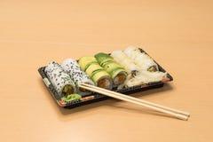 Traditionell japansk mat - del av flera sorter av sushi med wasabi och den inlagda ingefäran på ett magasin och med träpinnar Royaltyfri Fotografi