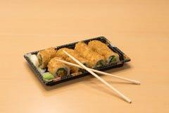 Traditionell japansk mat - del av flera sorter av sushi med wasabi och den inlagda ingefäran på ett magasin och med träpinnar Royaltyfri Bild