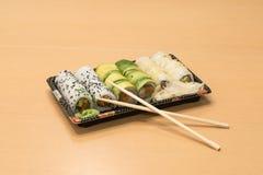 Traditionell japansk mat - del av flera sorter av sushi med wasabi och den inlagda ingefäran på ett magasin och med träpinnar Fotografering för Bildbyråer
