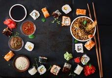 Traditionell japansk mat - sushi, rullar, ris med räka och sås på en mörk bakgrund Royaltyfri Foto
