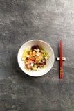 Traditionell japansk sallad i en vit platta med pinnar Royaltyfri Fotografi