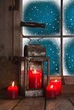 Traditionell julgarnering i rött: fyra brännande stearinljus de Arkivbilder