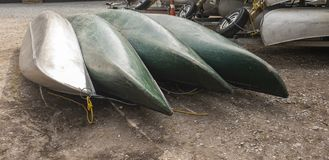 Traditionell kanot som är uppochnervänd på ett grusgolv bredvid floden royaltyfria bilder
