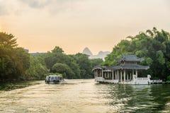 Traditionell kinesisk paviljong vid sjön på solnedgången, Guilin royaltyfria foton