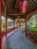 Traditionell kinesisk träkorridor i vibrerande rött med lyktor i den kinesiska trädgården i Pairi Daiza royaltyfri fotografi