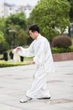 Traditionell klädd man som öva Tai Chi i en parkera, Yangzhou, Kina royaltyfri bild