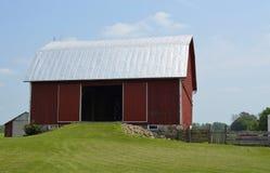 Traditionell ladugård och jordbruksmark Arkivbild