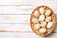 Traditionell mall för easter kort med omålade blandade organiska ägg i vide- korg med hö och dekorativa vildblommor Arkivfoton