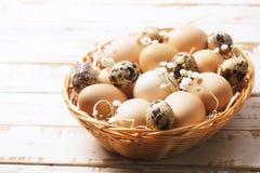 Traditionell mall för easter kort med omålade blandade organiska ägg i vide- korg med hö och dekorativa vildblommor Fotografering för Bildbyråer