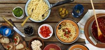 traditionell matitalienare Pastaspagetti med tomatsås, oliv och garnering med vin på trätabellen Arkivbilder