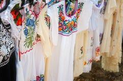 Traditionell mexicansk klänning på en försäljarestallskärm på Chichen Itza Arkivfoton