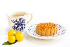 Traditionell mooncake med te och små tre apelsiner på sidor Royaltyfri Foto