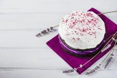 Traditionell påskpanettone- eller rysskulich med isläggning och lavendel på den violetta servetten och den vita trätabellen Royaltyfri Foto
